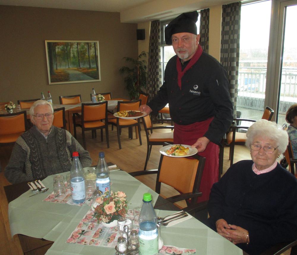 Koch serviert zwei Senioren das menü.