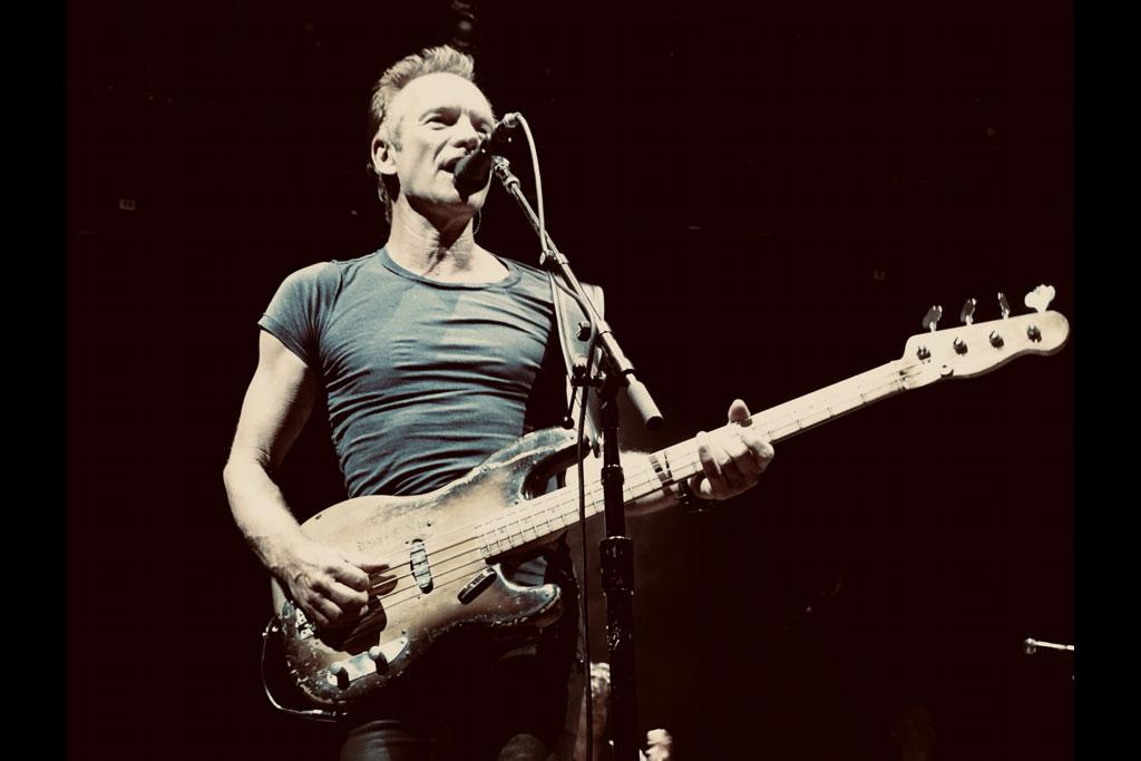 Sting mit Gitarre auf der Bühne.