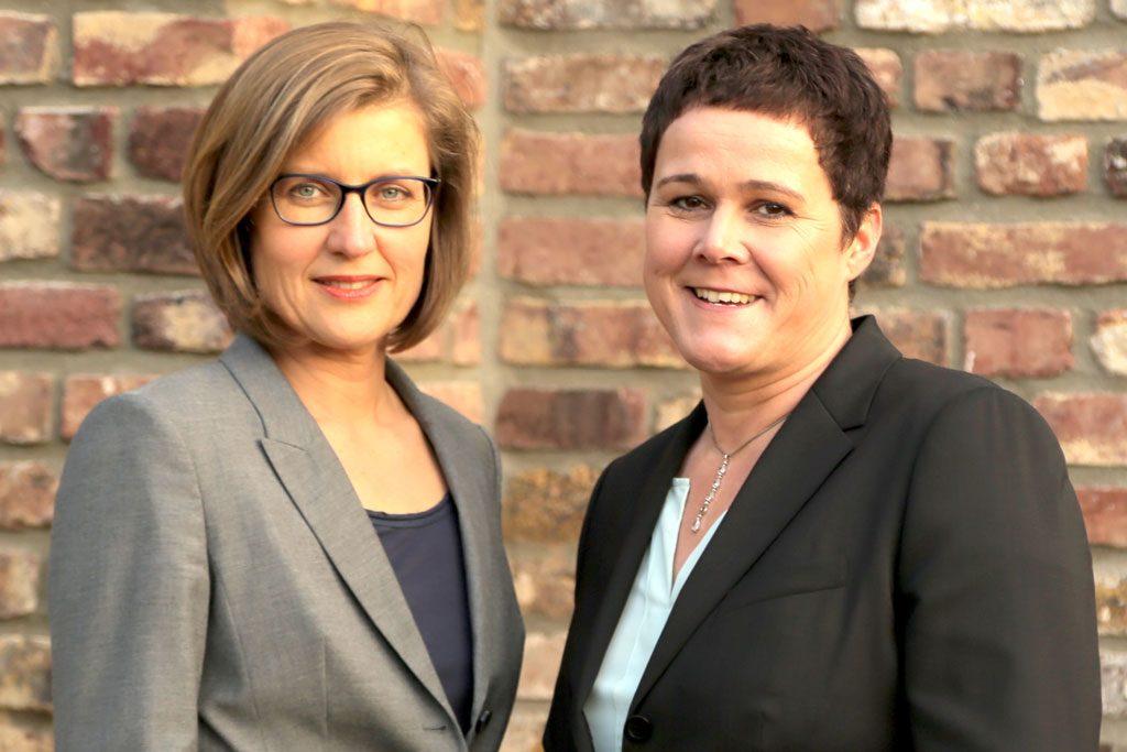 Zwei Frauen, im Hintergrund Backstein-Mauerwerk